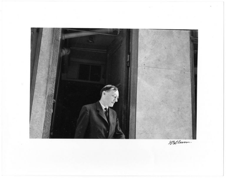 A b/w photograph by Harold Chapman of William Burroughs leaving the main entrance of the Beat Hotel, c. 1958/59. William S. BURROUGHS.