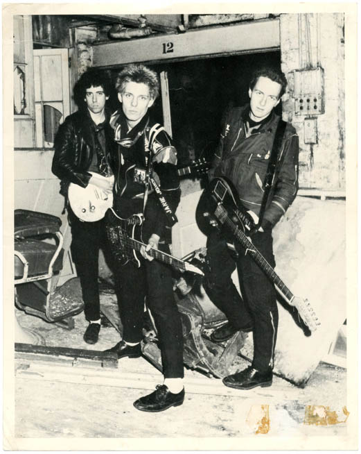 A commercially produced 10x8 b/w photograph of Mick Jones, Joe Strummer and Paul Simonon posing together with their guitars. The CLASH.