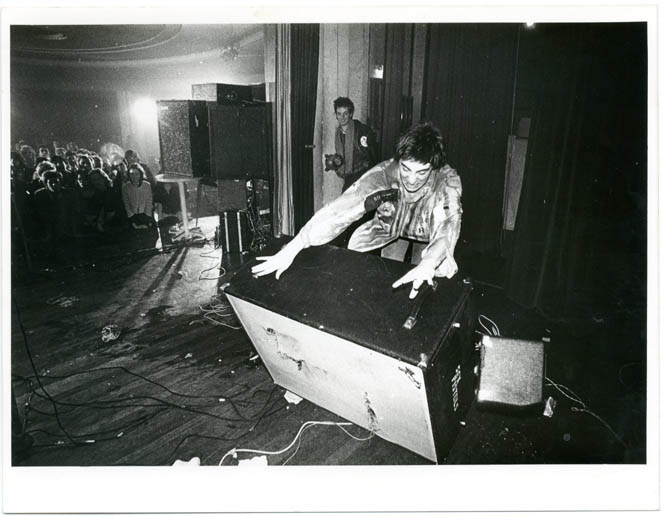 Original Ray Stevenson photograph of Glen Matlock manhandling the Fender speaker he had attacked with his guitar moments before at the Sex Pistols' Notre Dame Hall concert, London, 15th November, 1976. The SEX PISTOLS.