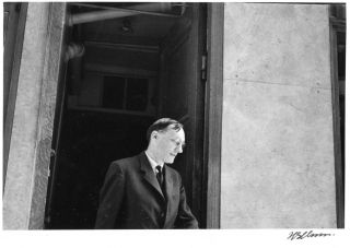 A b/w photograph by Harold Chapman of William Burroughs leaving the main entrance of the Beat Hotel, c. 1958/59.