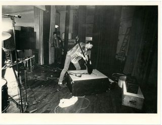 Original Ray Stevenson photograph of Glen Matlock slamming his bass guitar into an overturned...